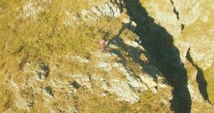 Orbitale radiale vlucht rond de jonge wandelende mens die zich bovenop de klip bevinden Kijkt weg stock video