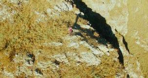 Orbitale radiale vlucht rond de jonge wandelende mens die zich bovenop de klip bevinden Kijkt weg stock videobeelden