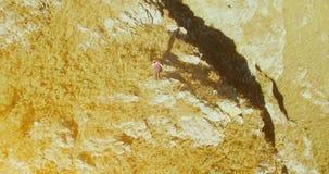 Orbitale radiale vlucht rond de jonge wandelende mens die zich bovenop de klip bevinden Kijkt weg stock footage