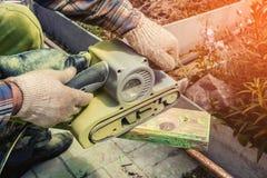 Orbitalslipmaskinarbete polerar maskin för wood hörn för träbräde en mald malande close upp tonat Royaltyfri Foto