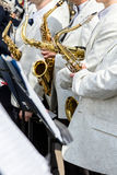 Orchestermusiker, die Saxophone vor dem Straßenkonzert halten Stockbilder