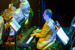 Orchestra con gli strumenti musicali e gli esecutori durante la prestazione Immagini Stock