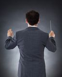Orchestra conductor with baton. Male Orchestra Conductor Directing With Baton Over Black Background Stock Photography
