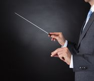 Orchestra conductor holding baton. Close-up Of Orchestra Conductor Hands Holding Baton Over Black Background Stock Photography