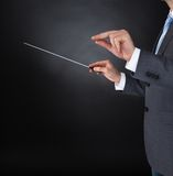 Orchestra conductor holding baton. Close-up Of Orchestra Conductor Hands Holding Baton Over Black Background Stock Photo