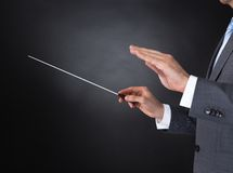 Orchestra conductor holding baton. Close-up Of Orchestra Conductor Hands Holding Baton Over Black Background Stock Photos