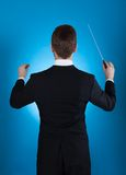 Orchestra conductor holding baton. Rear view of orchestra conductor holding baton against blue background Royalty Free Stock Photography