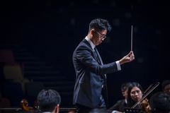Orchestra Conductor. A conductor leading an orchestra Stock Photos