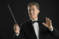 Orchestra Conductor Looking Away While Directing With His Baton. Mature male orchestra conductor looking away while directing with his baton against black Stock Images