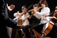 Orchestra conductor on stage. Conductor directing symphony orchestra with performers on background, hands close-up royalty free stock photography