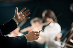 Orchestra conductor on stage. Orchestra conductor directing symphony orchestra with performers on background, hands close-up royalty free stock photo