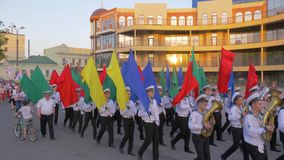 Orchestra of sailors walking along the main street of the city, students Marine Academy with colorful flags on parade. Kherson, Ukraine - May 20, 2019: Festival stock video footage