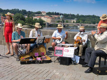Orchestra of street musicians play at Charles Bridge Stock Photos