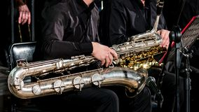 Orchestras in black clothes are sitting on chairs. Baritone saxophone on the musician`s lap. royalty free stock photos
