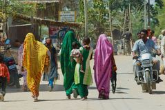 Indian women wearing colorful sarees walk by the street in Orchha, India. Orchha, India - March 27, 2007: Unidentified Indian women wearing colorful sarees walk stock photography