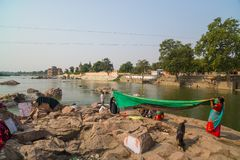 Women washing saree clothings into the river at Orchha, Madhya Pradesh, India. Royalty Free Stock Image