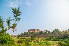 Orchha Palace, sunny day and blue sky, green landscape and cultivated fields around. Also spelled Orcha, famous travel destination. In India Royalty Free Stock Photography