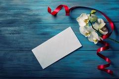 Orchidée et enveloppe blanches sur un bleu en bois Images libres de droits