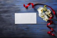 Orchidée et enveloppe blanches sur un bleu en bois Photographie stock libre de droits