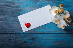 Orchidée et enveloppe blanches sur un bleu en bois Image stock