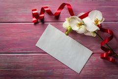 Orchidée et enveloppe blanches sur un fond en bois rose Photographie stock