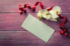 Orchidée et enveloppe blanches sur un fond en bois rose Image stock