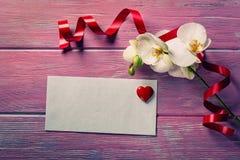 Orchidée et enveloppe blanches sur un rose en bois Photos libres de droits