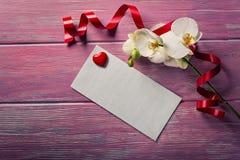Orchidée et enveloppe blanches sur un rose en bois Image libre de droits