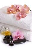 Orchidées roses, huile cosmétique et pierres de station thermale Photographie stock libre de droits