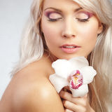 Orchid. Studio portrait of beautiful blond woman with orchid and professional eye makeup Stock Image