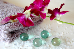 Orchid bath. Bath salts, beads, towel and purple orchids stock photo