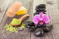 Orchid, bath salt, soap and black stones on weathered deck Royalty Free Stock Image