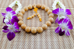 Orchid And Beads. Prayers beads with offerings of purple orchids Stock Photography