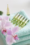 Orchid with beautys Ampules. Ampules with serum over towels Royalty Free Stock Image