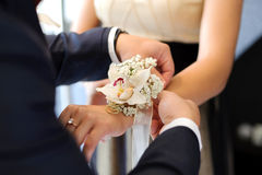 Orchid Boutonniere. Groom tying boutonniere to bridesmaid hand royalty free stock photo