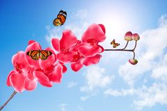 Orchid branch with pink flowers flying tropical butterflies against the sky with clouds