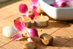 Orchid and candle spa. Orchid and candles for spa setting with white towel, displayed for an outdoor, evening massage session Stock Photos