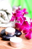 Orchid and candles with towels and pebbles Royalty Free Stock Photo