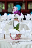 Orchid centerpiece on wedding tables. A purple orchid flower centerpiece on a white wedding table Royalty Free Stock Photos