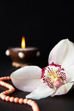 Orchid flower, coral beads and a burning candle on a black backg Royalty Free Stock Photo