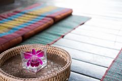 Orchid flower in glass. Thai backrest pillow on mat. Thailand sc Stock Photo