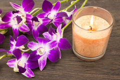 Orchid flowers and glass candle Royalty Free Stock Photo