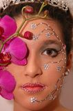 Orchid Girl. Girl wearing makeup made of rhinestone flowers with a pink orchid Royalty Free Stock Photography
