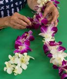 Orchid Lei making Hawaii. Orchid lei making for family ohana in Hawaii.  Sewing flowers or orchids together to make a lei for giving to family Royalty Free Stock Photos