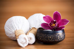 Orchid and massage compresses. Massage compresses called Luk Pra Kob with a purple orchid in a black decorative bowl Stock Photos