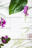 Orchid, notebook and decorative leaves Stock Images