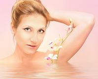 Orchid's wellness. A beautiful woman with orchids over tender background Royalty Free Stock Image