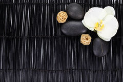 Orchid with zen stones and wicker balls on black background Royalty Free Stock Photography