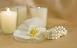 Orchidea bianca con le candele dell'aroma Immagine Stock