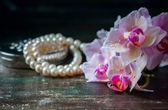 Orchidea rosa con una collana della perla fotografie stock libere da diritti